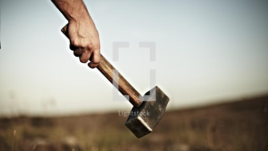 Hand holding a hammer