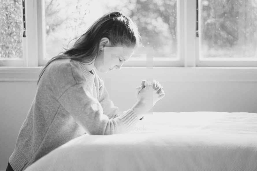 a woman kneeling in prayer by her bedside