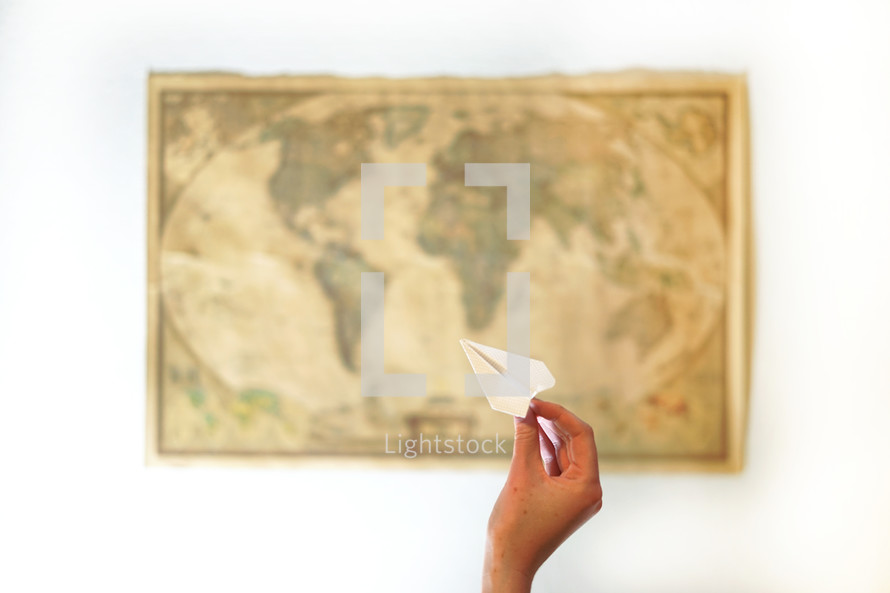 a woman throwing a paper airplane at a world map