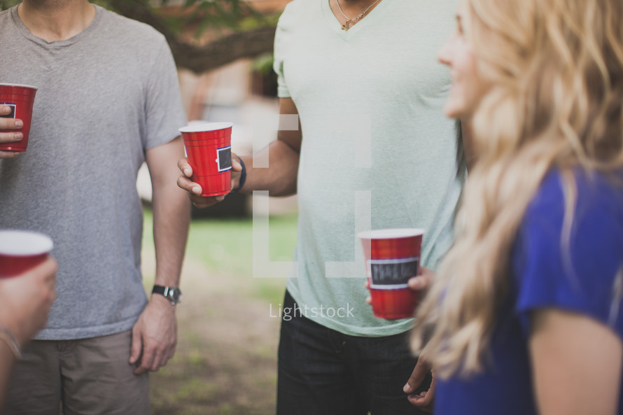 Friends standing outside holding drink cups.