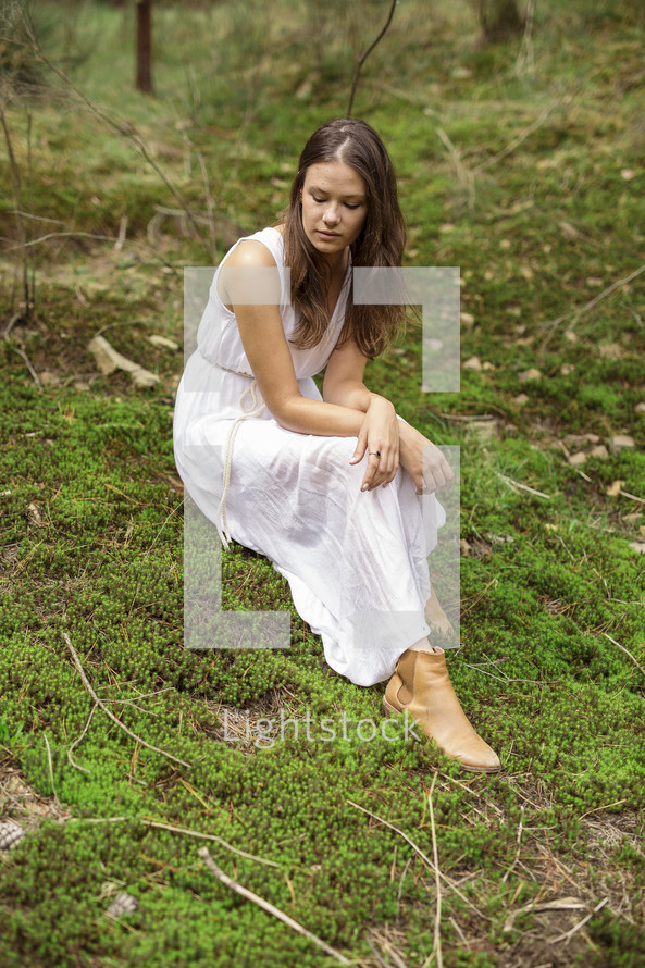 a woman in a dress sitting on mossy land