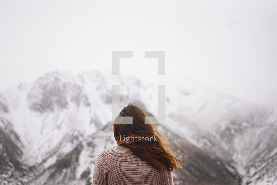 woman looking out at fog over snow capped mountains