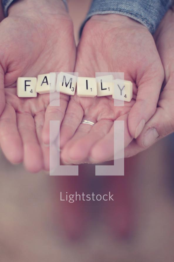 """Hands holding letter tiles spelling """"family."""""""