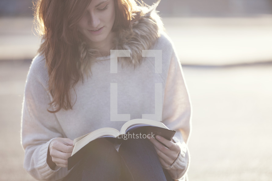 Woman sitting and reading the Bible outside.