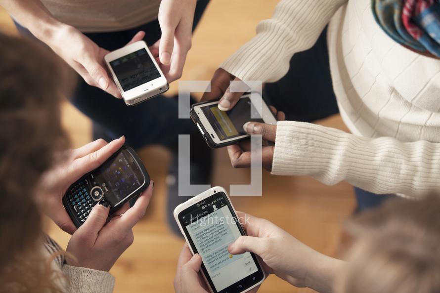Hands texting on smart phones.