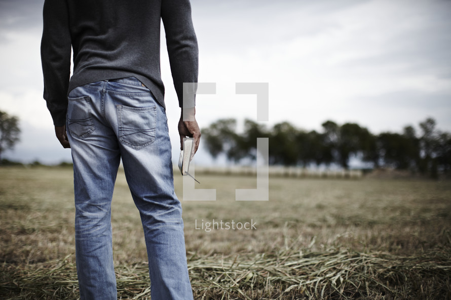 Man standing in a field holding his bible