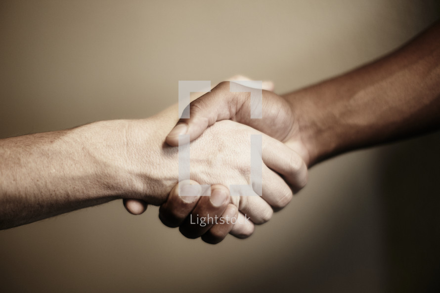 A handshake between a white and black man.