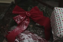 Red bow and wrapped Christmas presents with snow.