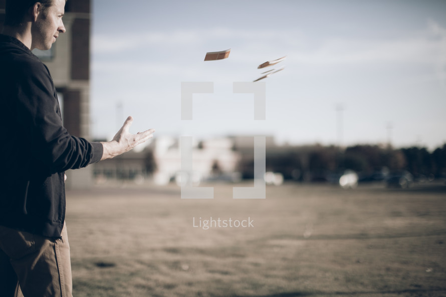 Man standing in grassy field with buildings in the background throwing a pile of cards into the wind.