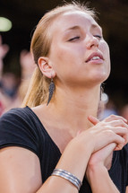 Close up of woman with eyes closed and face towards the sky with hands in praying position with other peopel behind her.