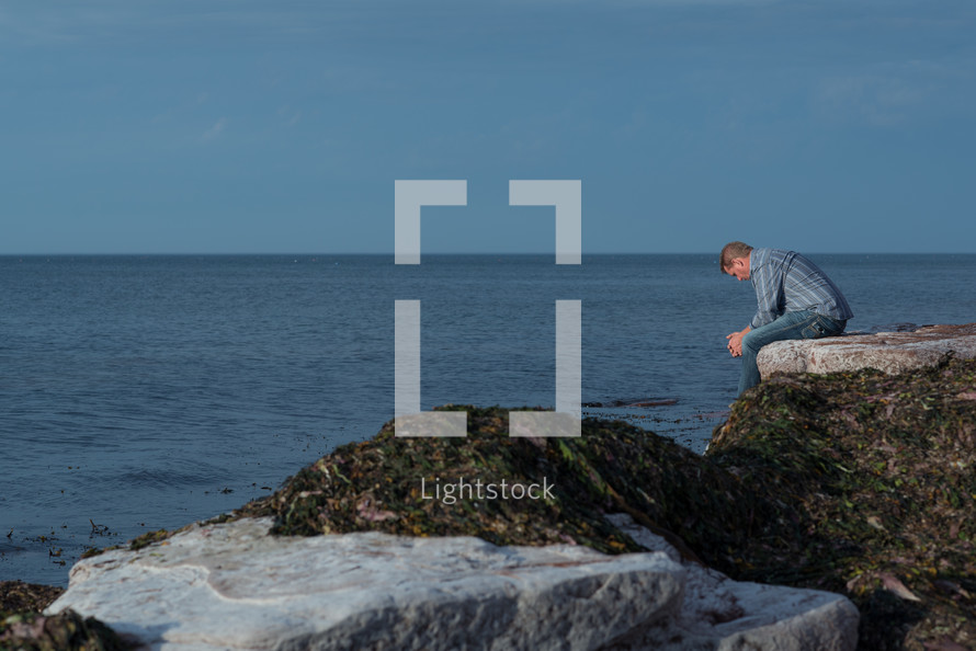 a man sitting on rocks along a shoreline