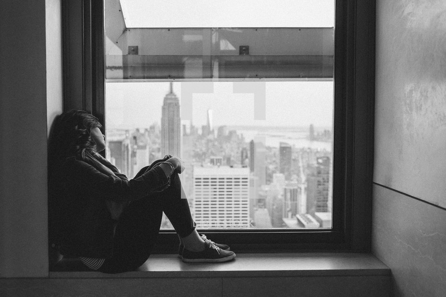 woman looking out a window at city skyscrapers