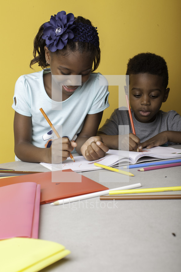 a boy and girl coloring on paper