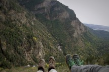 feet hanging off of the side of a mountain