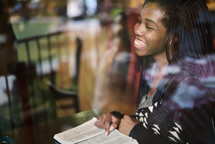 African American woman reading a Bible sitting in a window seat in a coffee shop