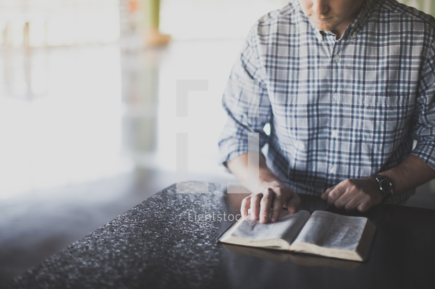 torso of a man reading a Bible