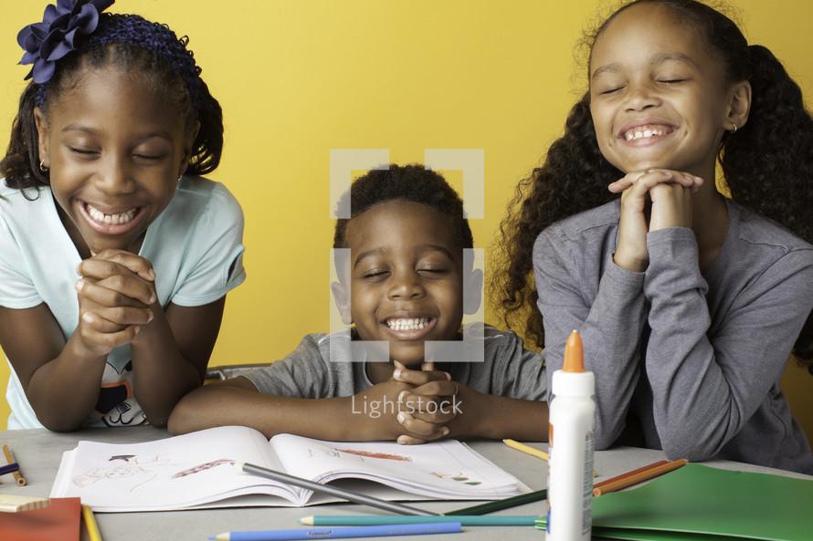 kids praying around a table