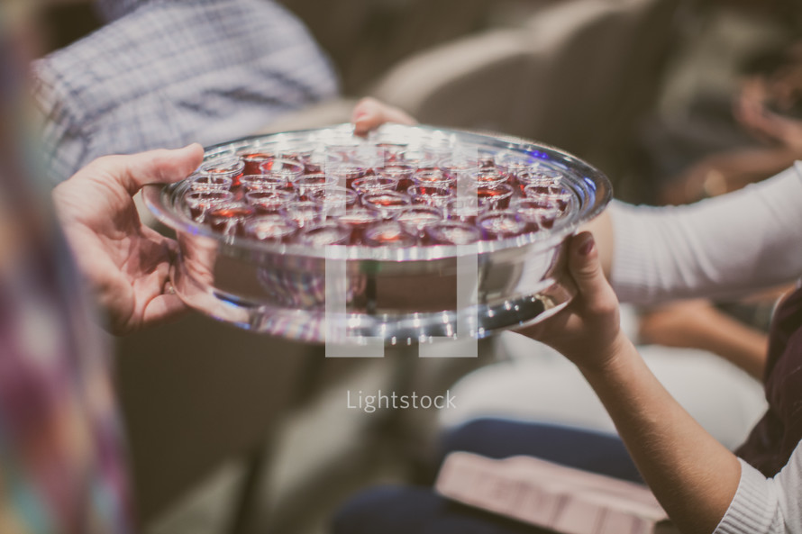 passing a tray of communion cups during a worship service