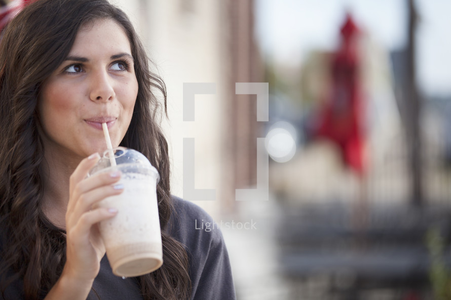 woman drinking an iced coffee