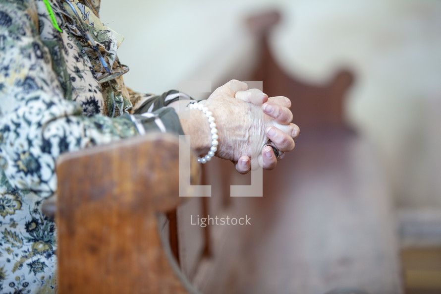 elderly woman's praying hands over a pew