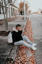 a man sitting on a curb in fall