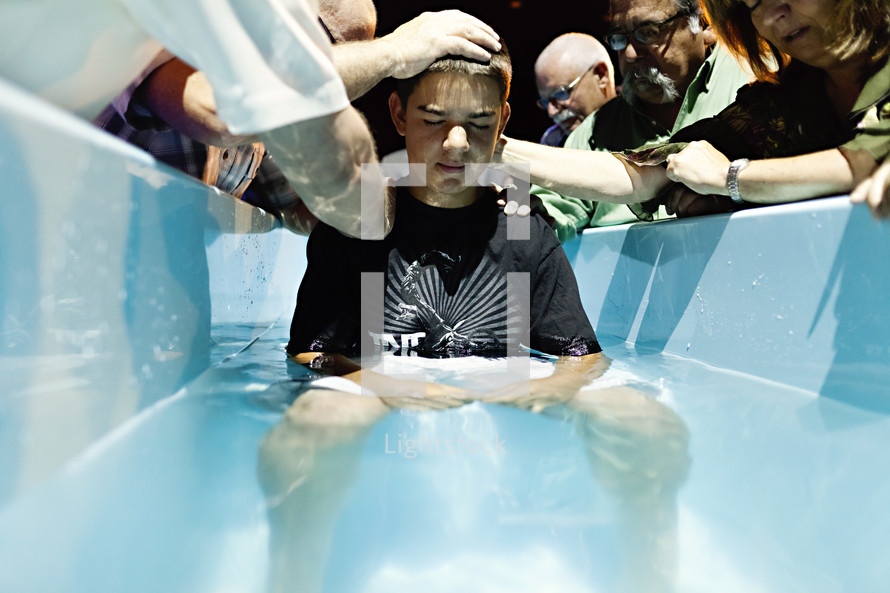 A boy being prayed over in a baptistry lying hands healing