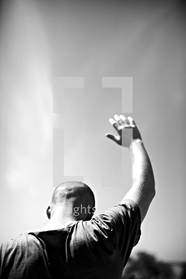 A man raising his hand in prayer
