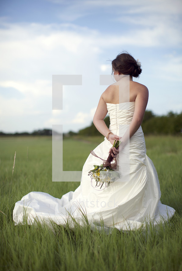 Bride holding bouquet outdoors