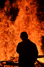 silhouette of a man in front of a raging fire