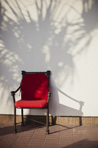 A red chair against a wall