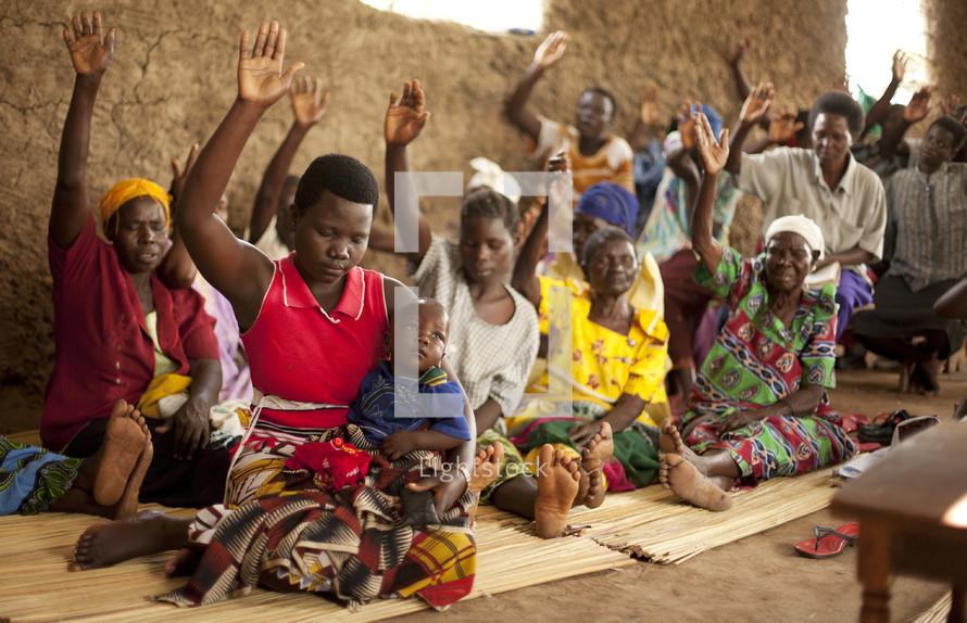 A group of Ugandan women lift their hands in prayer