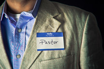 "Man wearing ""pastor"" name tag"