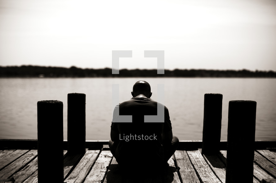 A man sitting on a dock praying