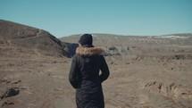 a woman walking over a barren landscape