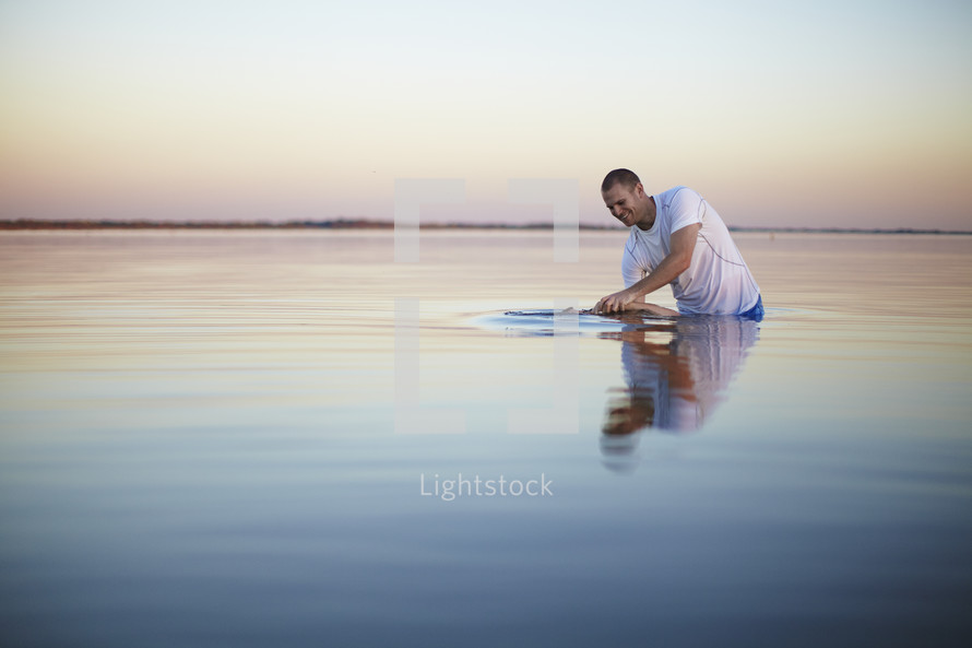 Man being baptized in a lake