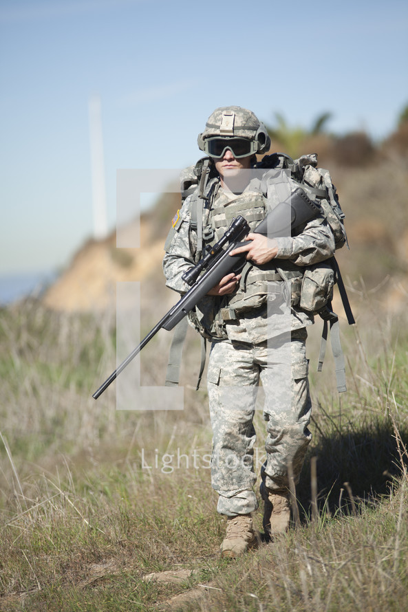 soldier walking carrying a rifle
