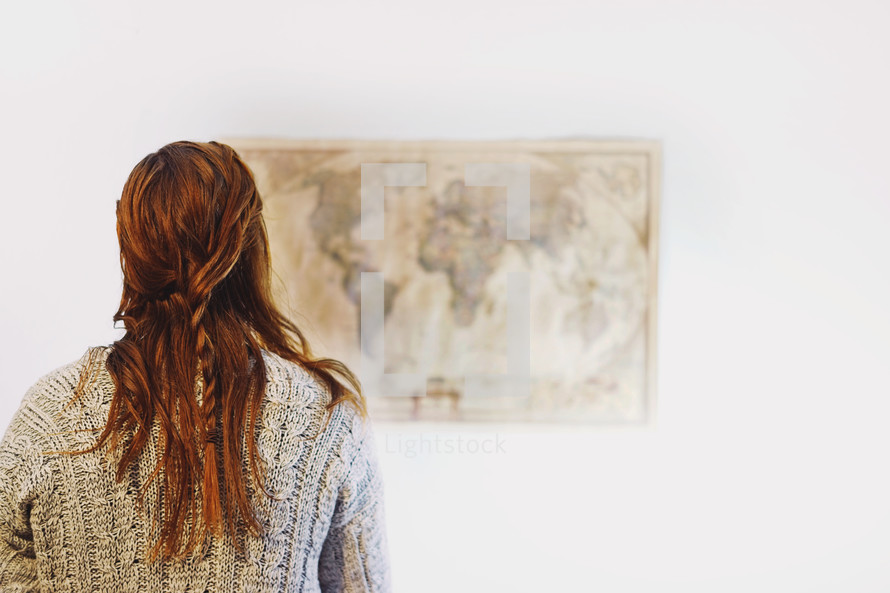 a woman looking at a world map on a wall