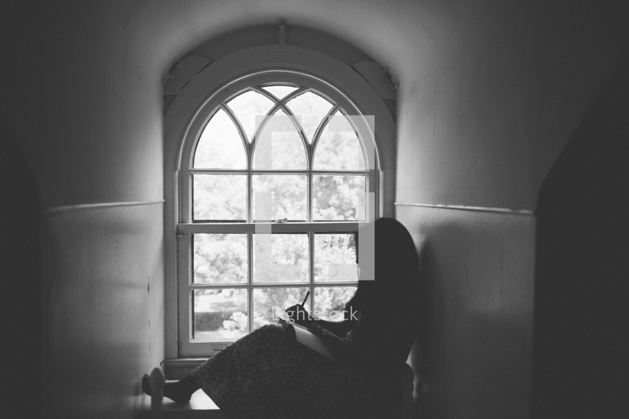 woman sitting in front of a window writing