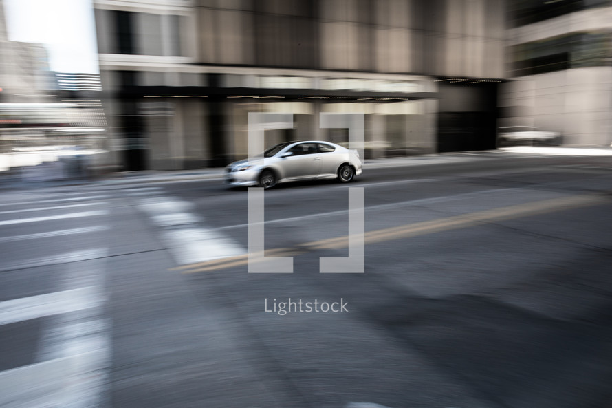 Panning shot of car on a city street which can give a sense of speed, urgency or even turmoil.