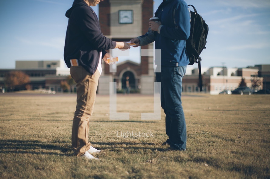 A man handing out a tract on a college campus