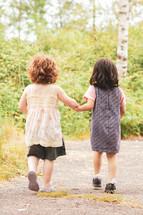 toddler girls walking holding hands