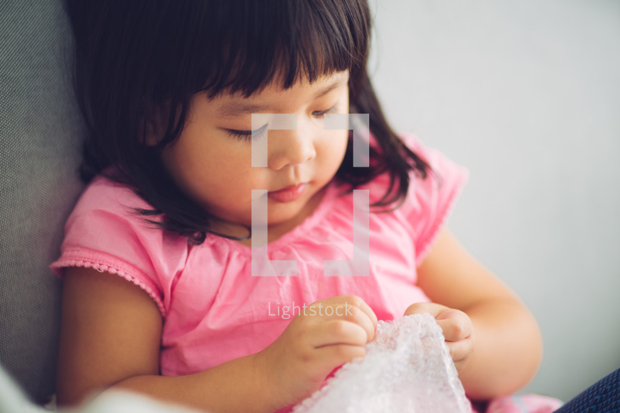 child holding onto a blanket