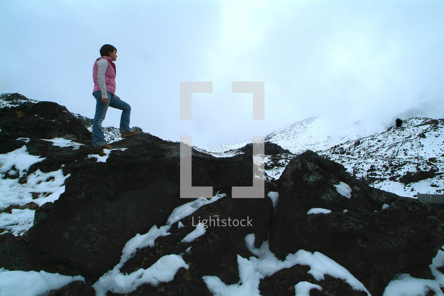 A woman hiking up a snowy mountain