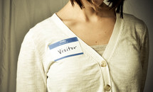 woman wearing a name tag with the words VISITOR