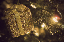 gold present ornament hanging on a Christmas tree