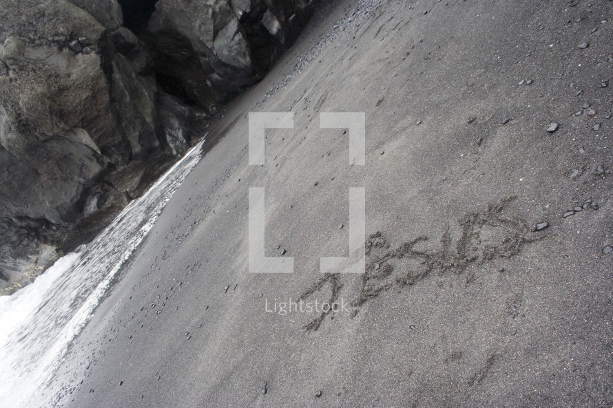 The word Jesus spelled out on beach