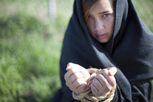 Girl in cape with hands bound with rope.