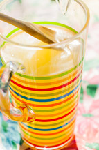 A striped pitcher full of lemonade wood spoon