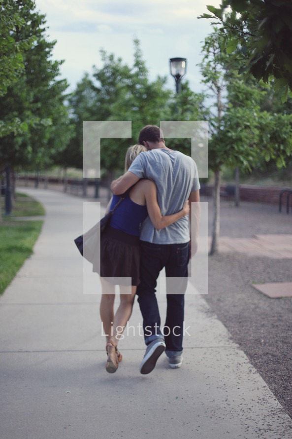 Man and woman embracing as they walk along sidewalk through park.