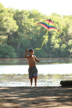 Boy flying kite by the river